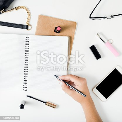 831932306 istock photo Close up woman hands writing in notebook in flat lay style on white table with female accessories. Concept feminine working place 843554090