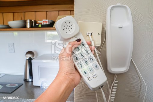 istock close up woman hold landline telephone at the house wall 882859590