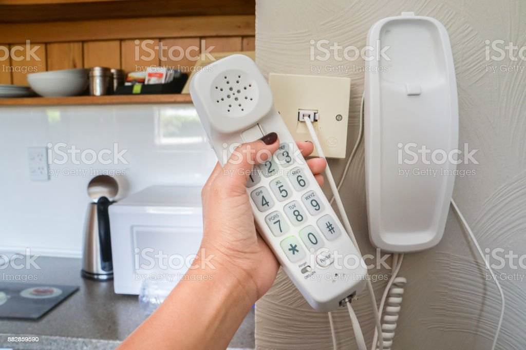 close up woman hold landline telephone at the house wall stock photo