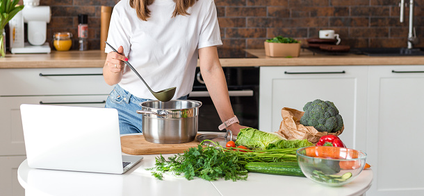 Close up woman in white t-shirt cooking soup with fresh vegetables in kitchen at home. Menu, recipe book banner. Girl reads the recipe in laptop. Caucasian model using internet in loft apartment.