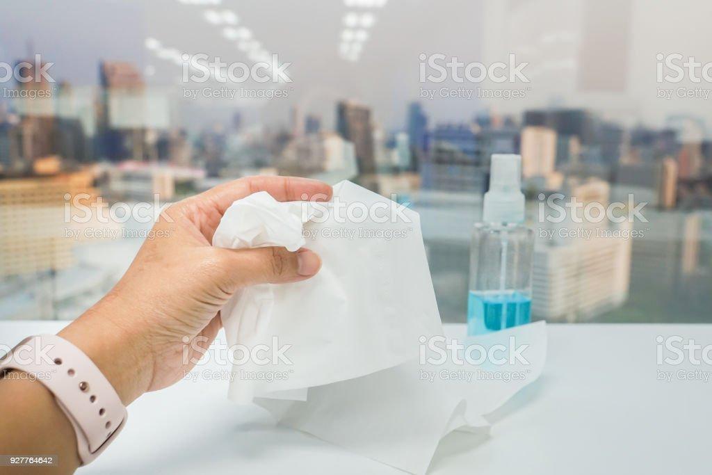 close-up mulher mão esquerda mantém papel de tecido com garrafa de álcool para a saúde e sanitárias - foto de acervo