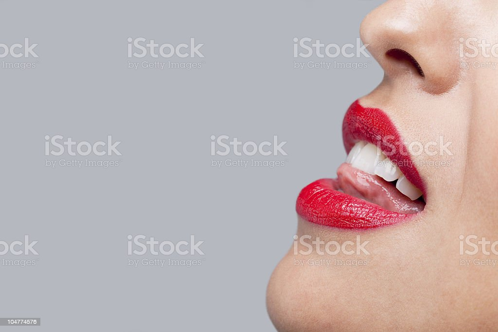 Close up woman licking her red teeth. royalty-free stock photo
