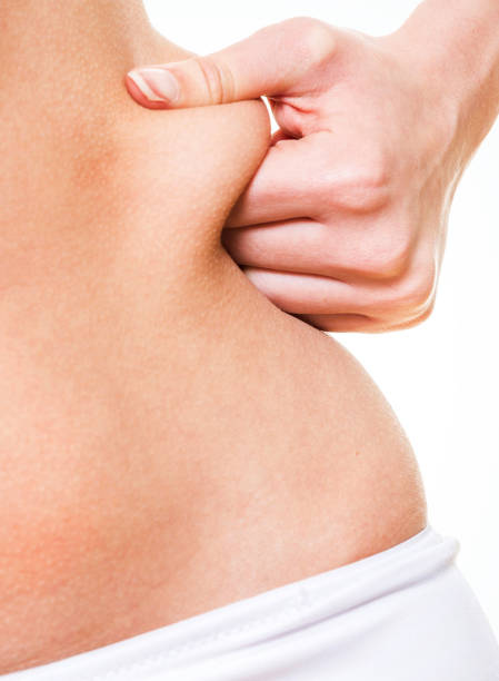 Close up woman pinching skin of her hip stock photo