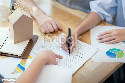 Close up, woman putting signature on document loan contract, real estate purchase, hands of woman sale represent point document to sign, contract deals success business.