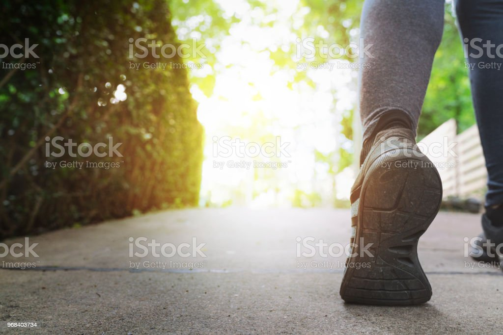 Close up woman running shoes, jogging on the road in a park, sport and health lifestyle concept stock photo