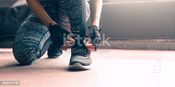 istock Close up woman sitting with hands lacing up sneakers shoes about healthy lifestyle concept. 843241142