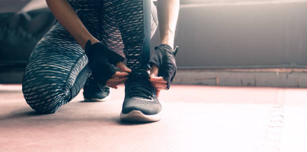 frau sitzt mit händen schnürung sneaker schuhe über gesunde lebensweise konzept hautnah. - fitness herausforderung stock-fotos und bilder