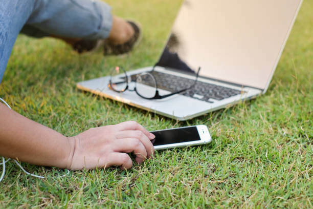 close up woman with smartphone laptop sitting and relaxing at the garden in the evening:chilling girl concept. - free images for downloads stock photos and pictures