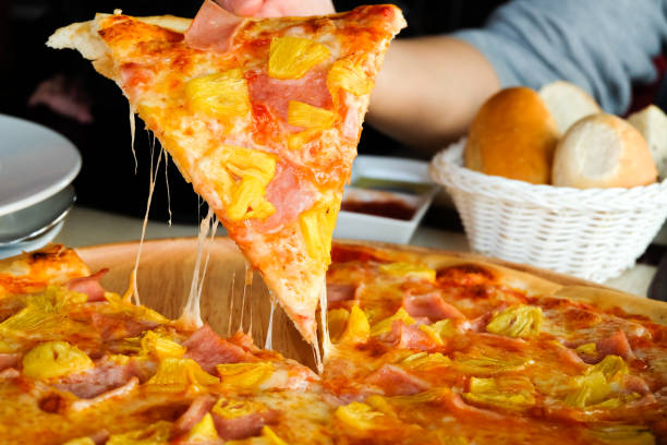 Close up Woman's hand picked Hawaiian pizza from a wooden tray on the table. stock photo