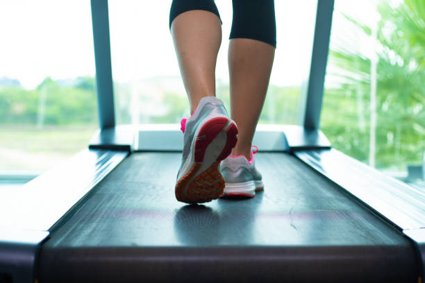Close up womans legs in pink sneakers on a. Treadmill in the gym Close up womans legs in pink sneakers on a. Treadmill in the gym. treadmill stock pictures, royalty-free photos & images