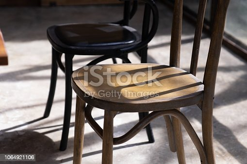 close up wooden chair seat with shadow and light on grunge cement ground