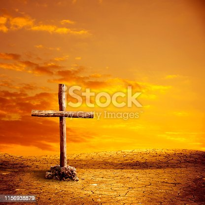 close up wooden cross on dried landscape over orange colored sunset sky