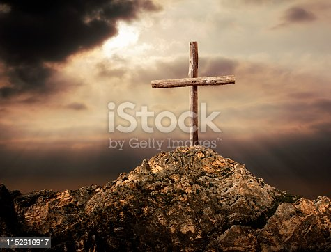 close up old-fashion simple wooden cross on rocky hill over cloudy sunset sky