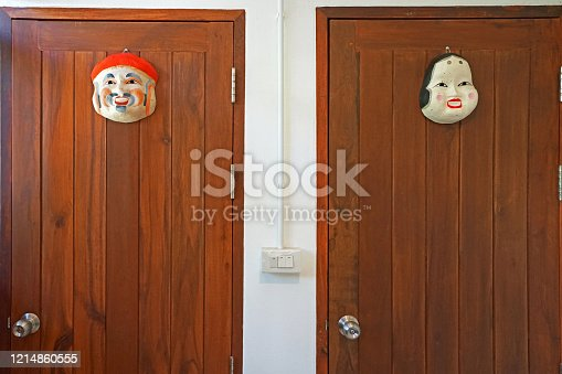 487881729 istock photo Close up wooden public restroom door separated by traditional Japanese mask 1214860555