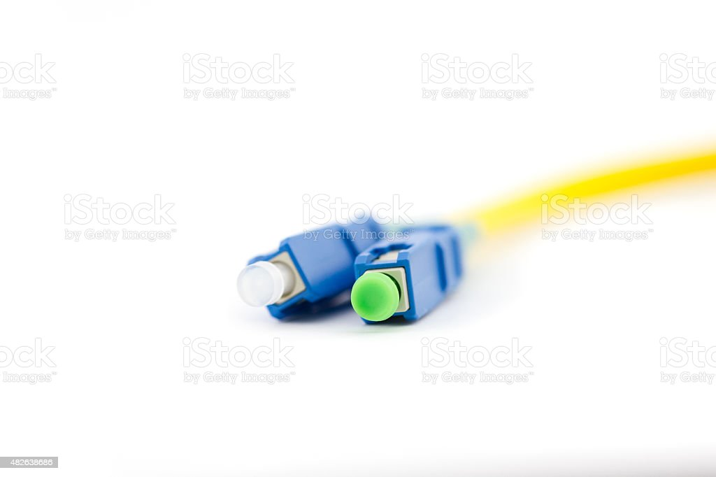 Close up yellow optic cable with blue patch cord connectors stock photo