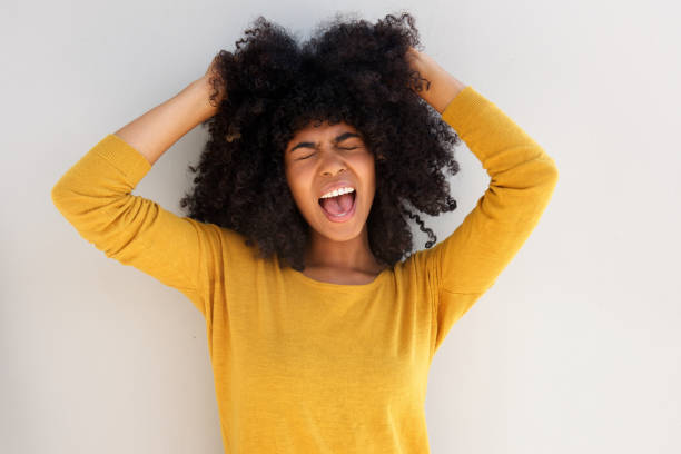 Close up young african girl screaming and pulling her hair against white background stock photo