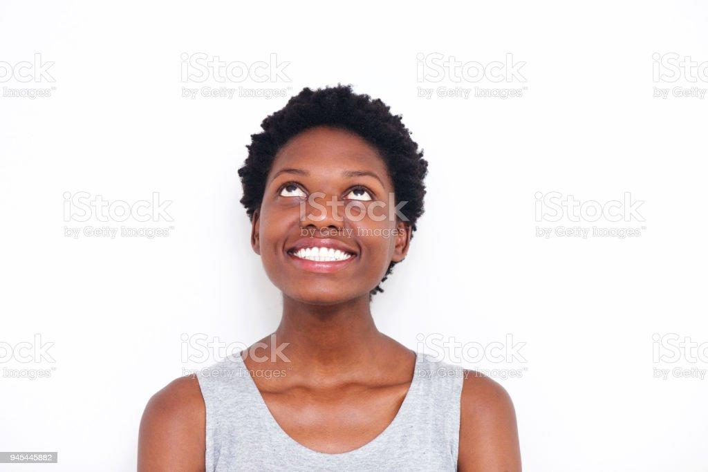 Gros plan jeune femme africaine en levant et souriant sur fond blanc - Photo