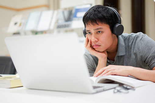 istock close up young asian man hand on chin with feeling bored while listening online course from webinar for midterm or final test at library room , education lifestyle people concept 1174243871