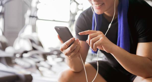 feche acima do homem asiático novo que prende o smartphone e escolhe a lista de reprodutor de música para escutar após o exercício do revestimento na ginástica, conceito saudável do estilo de vida - comodidades para lazer - fotografias e filmes do acervo