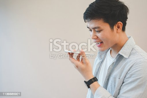 istock close up young asian man holding smartphone and using voice control for search data information  or access application , people  technology concept 1136685921