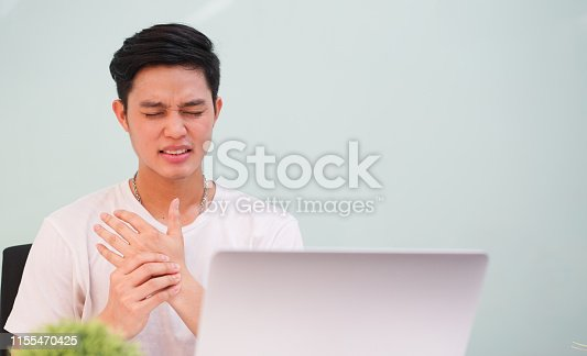 close up young asian man massage on his hand and arm for relief pain from hard working ,carpal tunnel syndrome concept