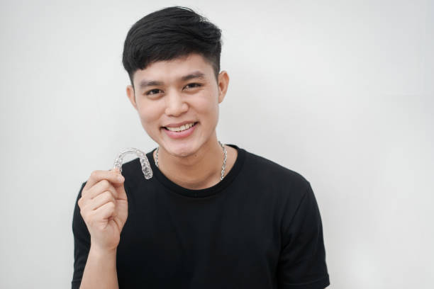 close up (isolated) young asian man smiling with hand holding dental aligner retainer (invisible) at white wall background of dental clinic for beautiful teeth treatment course concept - brace stock pictures, royalty-free photos & images