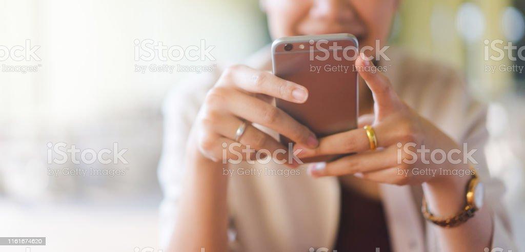 特寫年輕美麗的亞洲女人看智慧手機的視頻線上聊天與朋友或上網衝浪或玩移動應用程式在放鬆的時間,千禧年技術生活方式的概念 - 免版稅20多歲圖庫照片