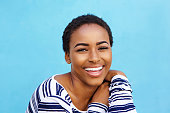 istock Close up young black fashion woman smiling against blue wall 857961068