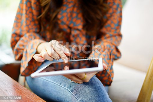 istock close up young businesswoman hand touch on tablet screen for reading news or swipe for play social media or shopping online at web browser , lifestyle concept 1047413656