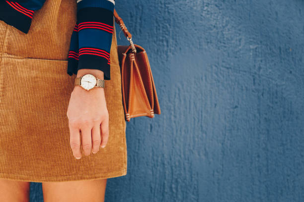 close up, young fashion blogger wearing a corduroy dress and a white and golden analog wrist watch. checking the time, holding a beautiful  leather purse. - corduroy stock pictures, royalty-free photos & images