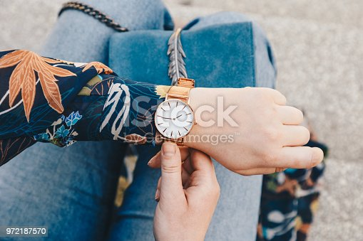 istock close up, young fashion blogger wearing a floral jacker, and a white and golden analog wrist watch. checking the time, holding a beautiful suede leather purse. 972187570