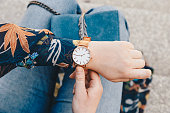 close up, young fashion blogger wearing a floral jacker, and a white and golden analog wrist watch. checking the time, holding a beautiful suede leather purse.