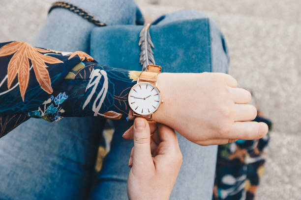 close up, young fashion blogger wearing a floral jacker, and a white and golden analog wrist watch. checking the time, holding a beautiful suede leather purse. stock photo