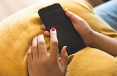 istock Close up young female using smartphone on sofa. technology communication and modern life concepts 1144853492