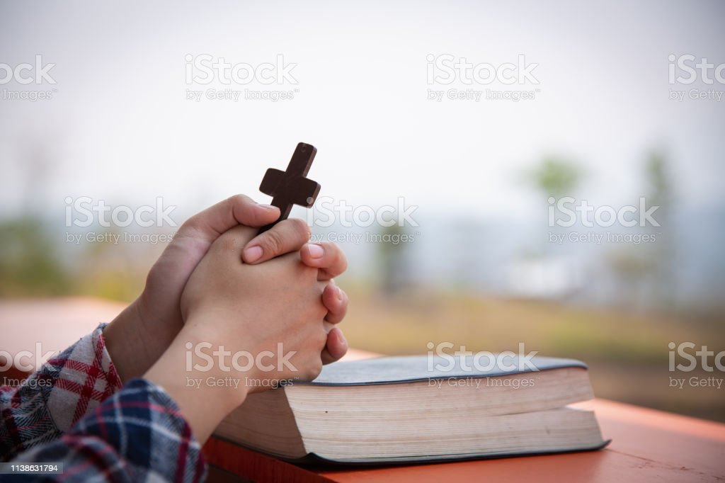 ab146b8e0 Close up young hands holding wooden cross over holy bible and praying.  christian concept - Stock image .