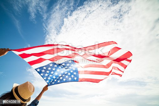 istock Close up young happy woman holding United States of America flag and running, jumping carefree with open arms with blue sky. USA Independence day, 4 July. 992403616