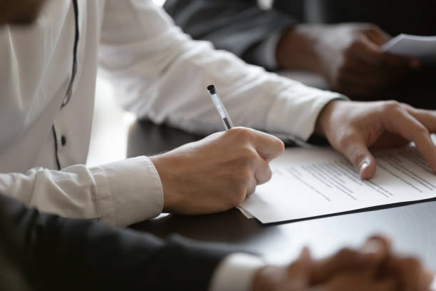 close up young male manager hands signing contract. - assertiveness stock pictures, royalty-free photos & images