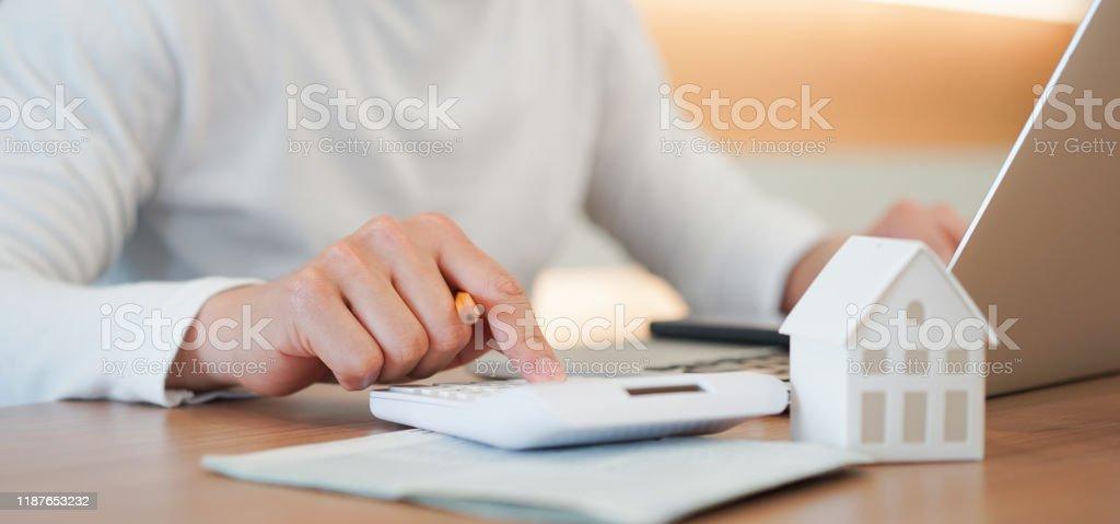 закрыть молодой человек стороны нажмите на калькулятор, чтобы проверить и суммарные расходы ипотечного жилищного кредита для рефинансиро� - Стоковые фото Аренда дома роялти-фри
