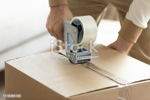 Close up young man holding tape dispenser, sealing big cardboard box with adhesive scotch. House removal service worker preparing packing homeowners belongings to moving day, relocation concept.