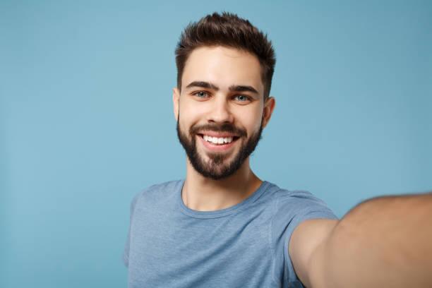 nahaufnahme junger lächelnder mann in lässiger kleidung posiert isoliert auf blauem wandhintergrund, studioporträt. menschen aufrichtige emotionen lifestyle-konzept. verspotten sie den kopierraum. selfie-aufnahmen auf dem handy. - selfie stock-fotos und bilder