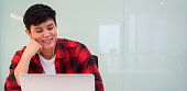 istock close up young student asian man wearing earphone and using laptop for watching movie in relaxation time after finished course at library university , lifestyle people concept 1144750331