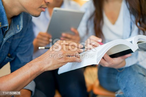 istock close up young thai student man hand using pencil and writing on book for explain and teach to friends at classroom , relationship and study concept 1141509628