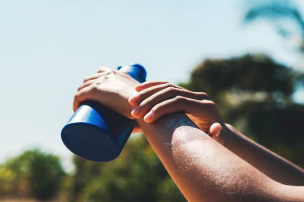 Nahaufnahme junge Frau Anwendung Sonnencreme Lotion auf der Hand mit blauen Himmel Hintergrund – Foto