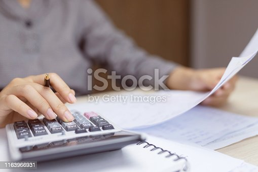 Close up young woman hand is writing in a notebook and using calculator counting making notes Accounting at doing finance at home office. Savings finances concept. note pad