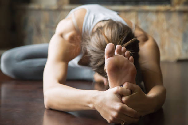 close up young woman in janu sirsasana pose, home interior - stretching stock photos and pictures