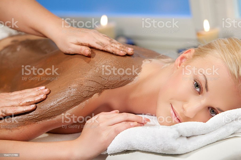 Close up young woman recieving a chocolate massage royalty-free stock photo