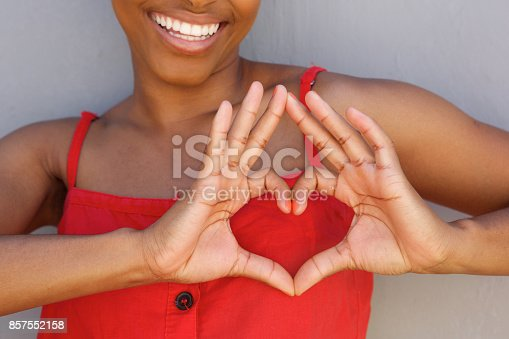 istock Close up young woman smiling with heart shape hand sign 857552158