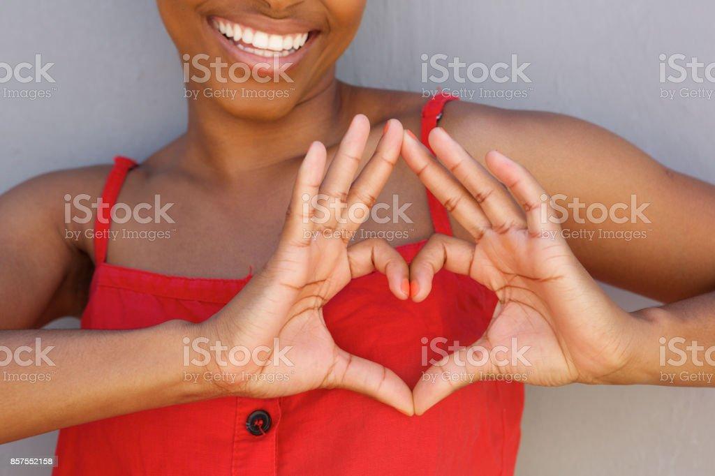Gros plan jeune femme souriante avec signe de main forme coeur - Photo