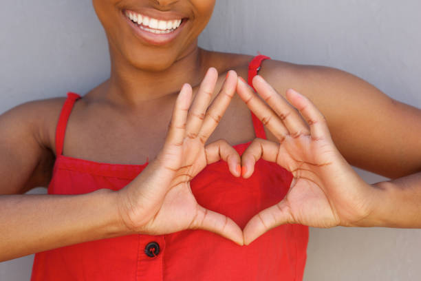 close up young woman smiling with heart shape hand sign - heart shape stock photos and pictures