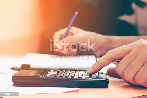 Close up young woman with calculator counting making notes at home, hand is writes in a notebook. Savings, finances, concept.